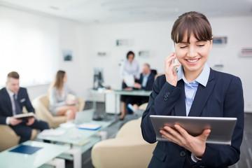 Geschäftsfrau telefoniert und schaut auf Tablet PC