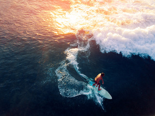 Wall Mural - Aerial view of the young man surfing the wave at sunset