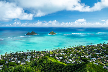 Mokulua islands surrounded by torquise water of the Pacific Ocean and green coast of Oahu, Hawaii