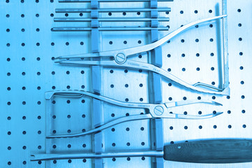 Detail shot of steralized surgery instruments with a hand grabbing a tool take with art lighting and blue filter