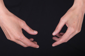 expressive slender skinny female hands in various poses on a black background