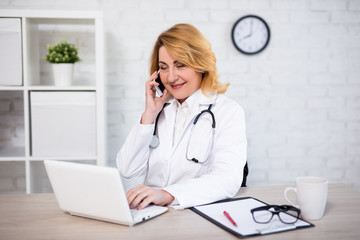 cheerful mature woman doctor or nurse working with laptop and talking by phone in office