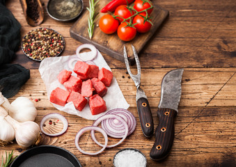Raw lean diced casserole beef pork steak with vintage meat hatchet and knife and fork on wooden background. Salt and pepper with fresh rosemary, red onion and garlic with rosemary