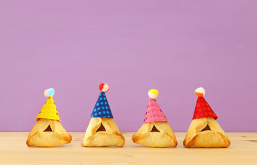 Purim celebration concept (jewish carnival holiday). Traditional hamantaschen cookies with cute clown hats over wooden table and purple background.