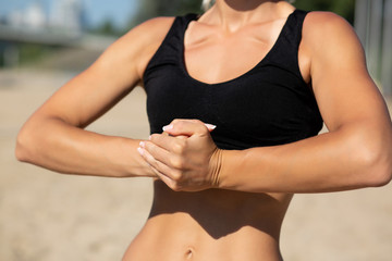 Pretty tanned fit woman stretching arms at the beach