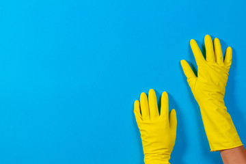 Hands in yellow gloves on blue background Wall mural