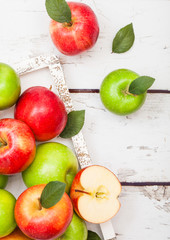 Fresh organic red and green apples with leaves on wooden background in wooden box