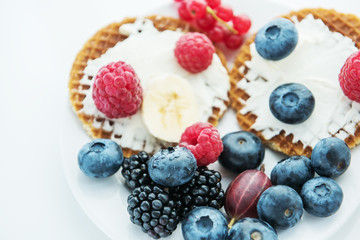 Waffles and various fresh berries and fruits. Healthy tasty breakfast, snack. Very soft selective focus.