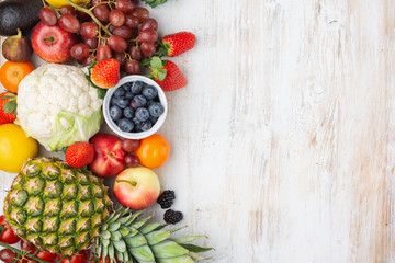 Healthy colorful fruits vegetables berries, strawberries oranges plums grapes broccoli cauiliflower mango persimmon pineapple on white wooden table, top view, copy space, selective focus