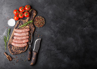 Raw beef and pork sausage on old chopping board with vintage knife and fork on black background.Salt and pepper with rosemary and tomatoes.Space for text