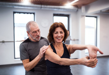 A senior woman in gym doing exercise with a personal trainer.