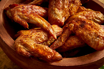 Close up of delicious grilled chicken wings in wooden bowl on wooden table.