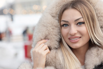 Beautiful pretty young blonde woman in winter. Woman smiling.
