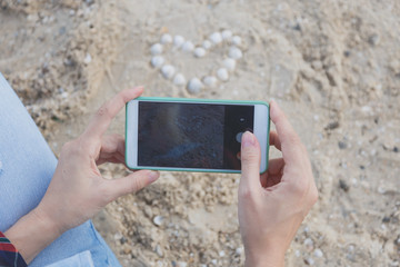 female hands with smartphones take pictures of shells on the sand in the form of a heart
