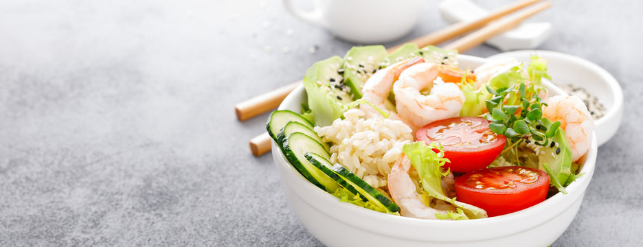 Hawaiian poke bowl with shrimps, rice and vegetables, healthy Buddha bowl with prawns, rice, avocado, cucumber, tomato and lettuce. Banner