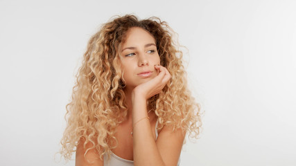 head and shoulders plan of blonde wooman with big curly hair in studio on white. Bored woman
