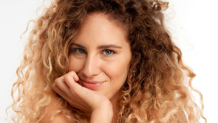 closeup portraitof green eyed model with big curly blonde hair, ideal skin watching to the camera and smiling slightly