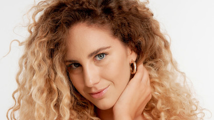 closeup portraitof green eyed model with big curly blonde hair, ideal skin touches her neck and watching to the camera