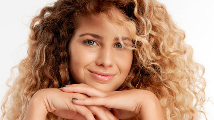 closeup portraitof green eyed model with big curly blonde hair, ideal skin smiling watching to the camera