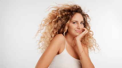 head and shoulders plan of model with big curly blonde hair in studio and blowing hair has flirty glance