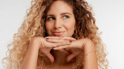 closeup portrait of blonde model with curly hair put her chin on two crossed hands and watching aside smiling