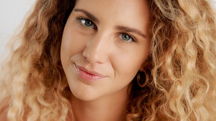 happy smiling, flirty glance closeup portrait of blonde model with ideal skin and cyrly hair
