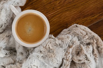 Blanket and coffee on wooden background