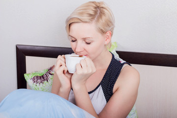 Young beautiful blonde girl with short hair sitting on her bed and holding a hot drink