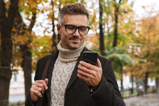 Photo of masculine man 30s wearing warm clothes walking outdoor through autumn park, and using mobile phone