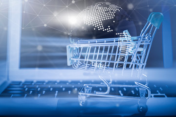 Online shopping concept. Closeup of shopping basket with digital globe and wireless digital line connection symbol on laptop. Business and technology.