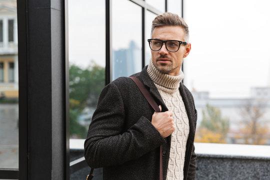 Portrait of stylish man 30s wearing eyeglasses, walking through city street near the building