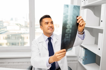 medicine, healthcare and people concept - smiling doctor with x-ray scan at hospital