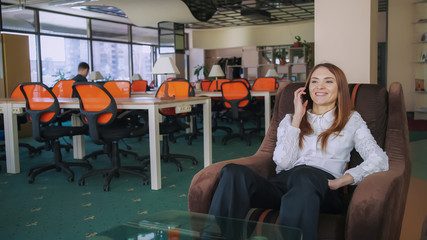 Woman phone to her boss. She using smartphone  speaking  with him about new project. Employee smile and happy. Female sitting in an armchair and relax in the office. She is satisfied her working day.