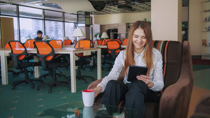 7ef8885e57 Business woman has coffee break at the office. Female using tablet for  searching information.