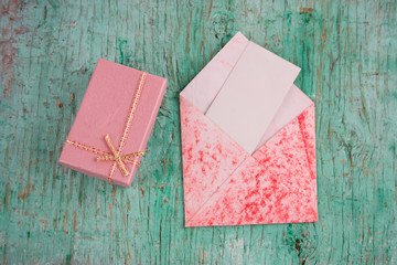 top view pastel pink present box and evelope with  white blank paper sheet with place for text on a mint green shabby background