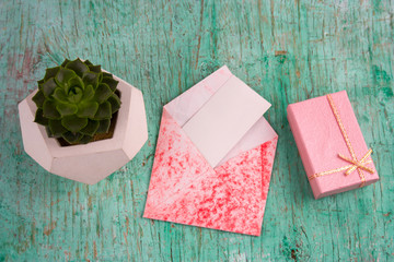 top view pink gift ,succulent potbox and envelope with white blank paper mock up shabby wooden background