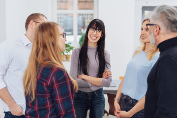 Happy woman leading team discussion in office