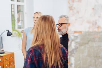 Three businesspeople standing listening