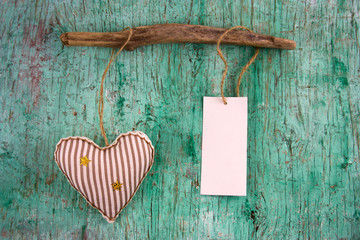 cute stripped soft toy heart and white paper label with place for text  on a vintage wall