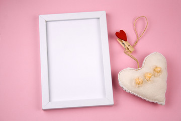 empty white frame with place for text and fabric stuffed toy in a shape of heart on a pastel pink background