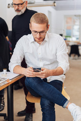Young businessman checking his mobile phone