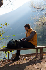 Man taking a rest on the bench by the lake while hiking in nature.