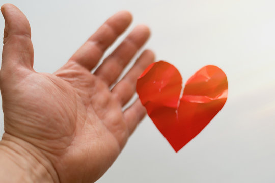 The concept of a broken heart, the end of love, rejection, divorce. The male hand let go of the damaged heart.