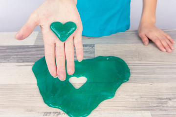 Girl created a heart shape slime with a cookie cutter and showing it on her palm