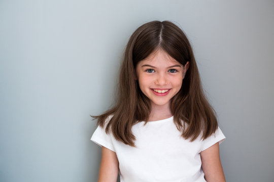 Portrait of a beautiful young girl in a white T-shirt on a gray background, concept advertising