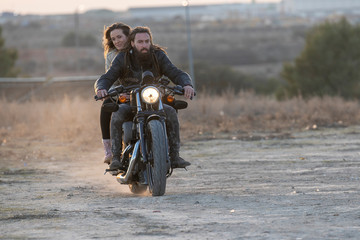 young man and blond woman driving classic motorbike on the field at sunset