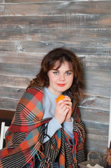 Beautiful and joyful woman with a plaid on her shoulders holding a mandarin