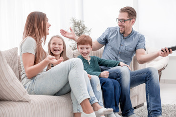 cheerful family sitting on the couch in the living room