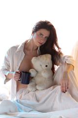 Reizende Frau mit Teddybär und Kaffee