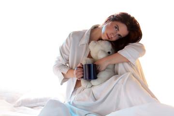 Frau mit Tasse und Teddybär am morgen